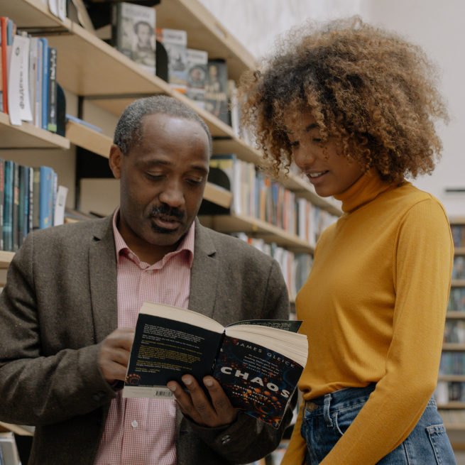 A teacher looks at a book with his student