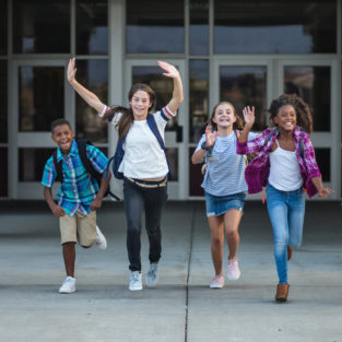 Four students run out of the school building happily