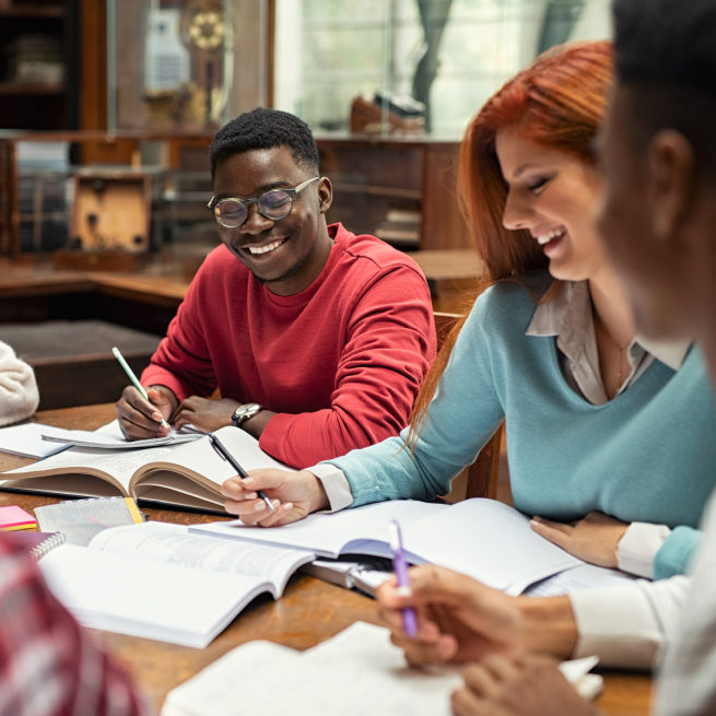 Students sit around a study room table laughing
