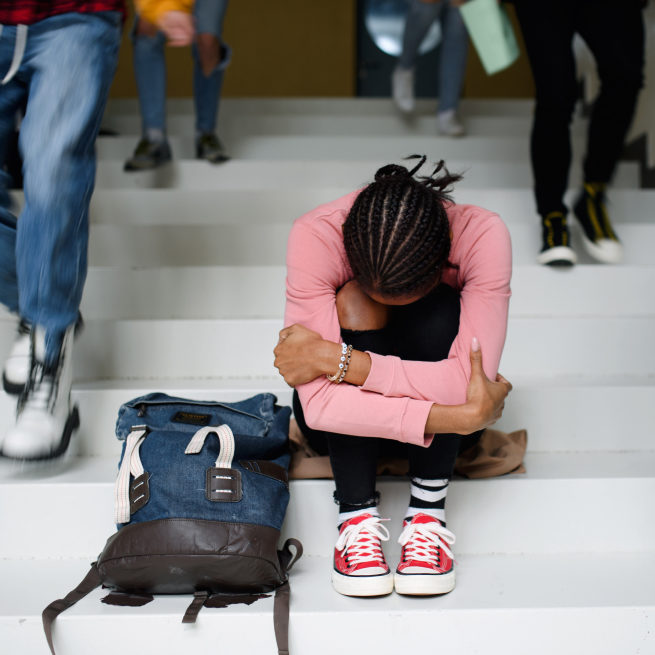 A student sits on a staircase with her head on her knees