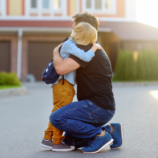 A man comforts a child in front of their house.